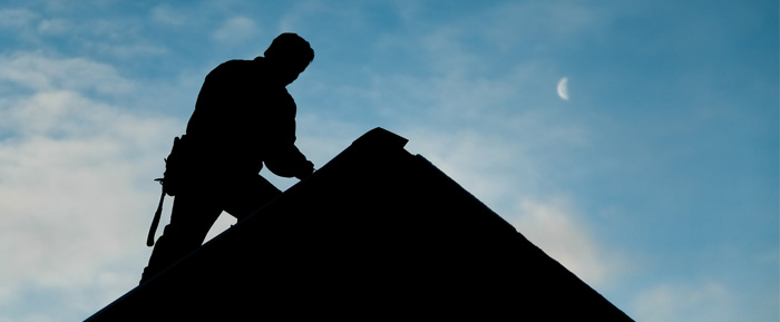 A photo silhouette of a roofer fixing a roof.
